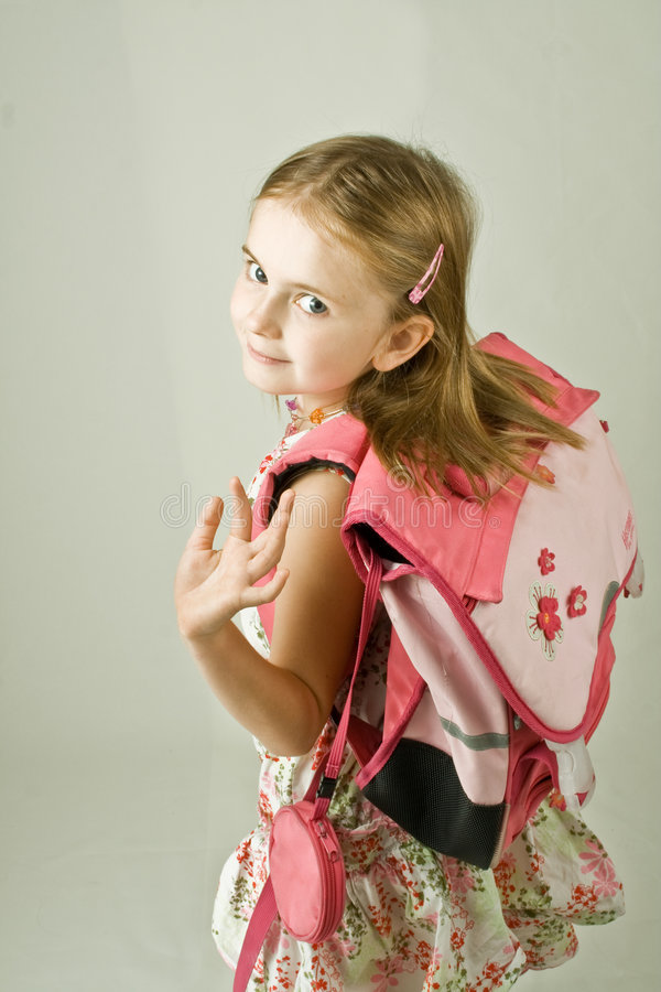 Back to School. Young girl in a print dress and a pink school bag on her back, turning back to wave goodbye. Three-quarters vertical portrait against a white royalty free stock images