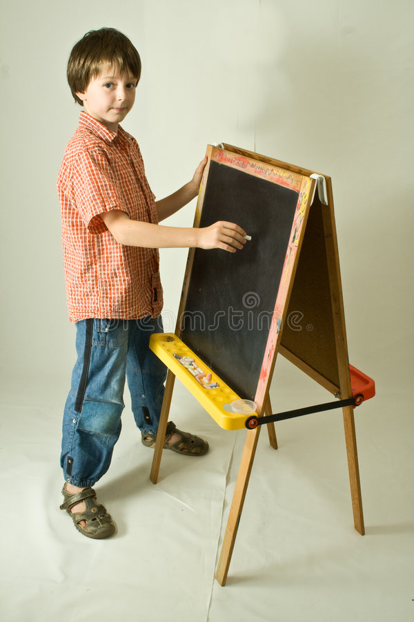 Back to School. Young boy about to write on a children's blackboard. Full-length vertical portrait isolated against a white background stock images