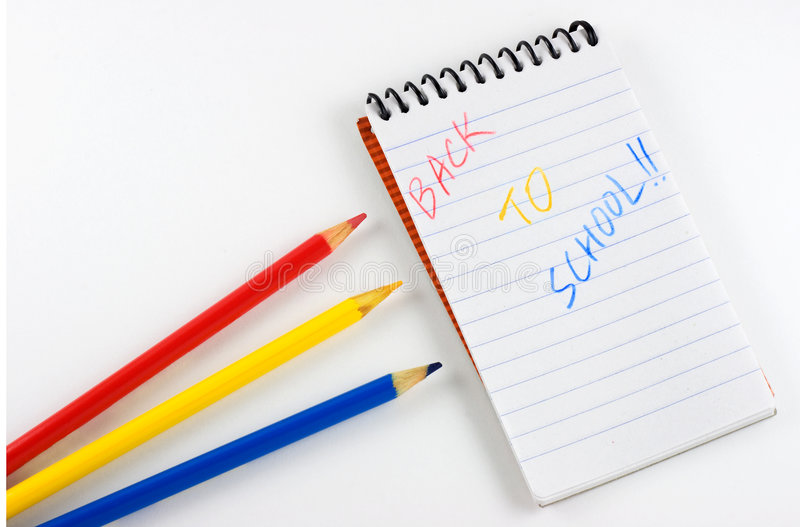 Back to School Notepad and Colored Pencils. Three sharpened colored pencils next to lined notepad with the words Back to School stock images
