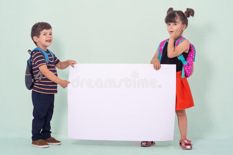 Back to school - advertisements. School Kids with backpacks holding white blank or white card. royalty free stock photography
