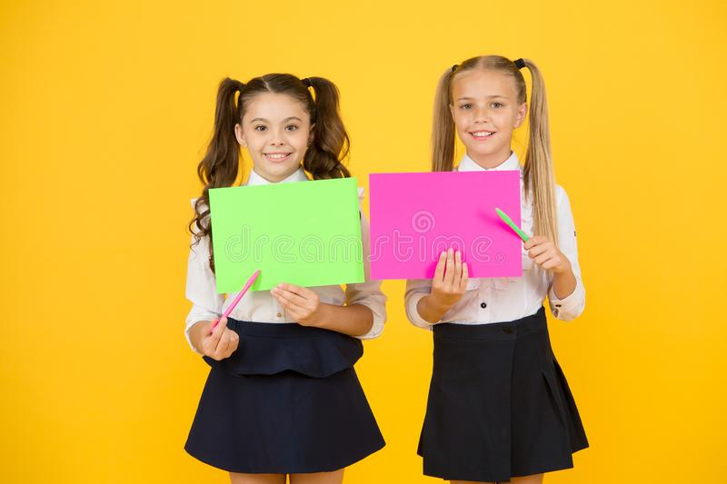 Back to school advertising. Happy school children pointing at blank sheets on yellow background. Small kids starting new stock image