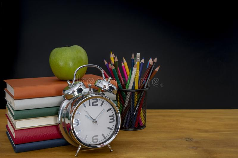 Back to school background with books and alarm clock over chalkboard royalty free stock photography