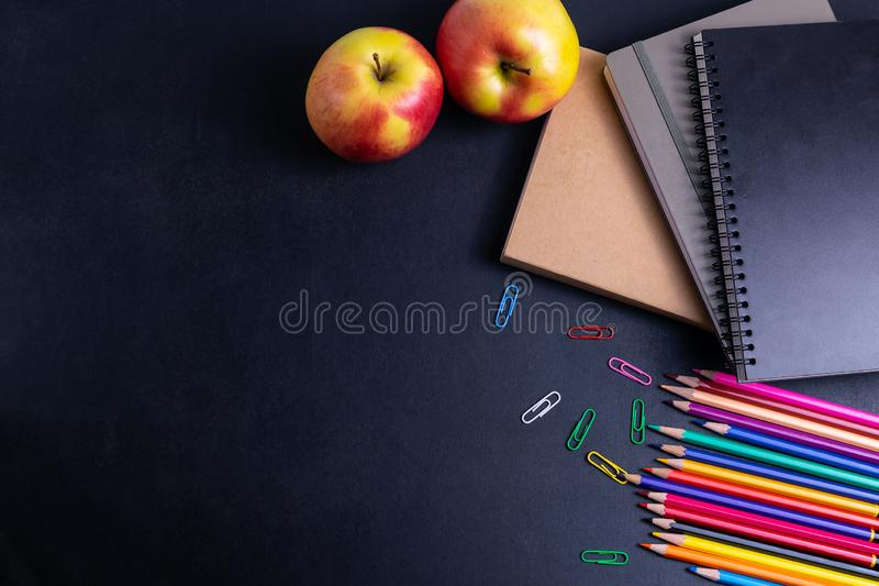 Back to school background with books and apple on blackboard flat lay royalty free stock photography