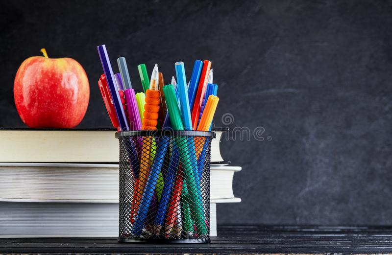 Back to school background with books and apple over blackboard with copy space stock photography