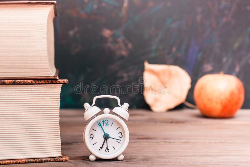 Back to school background with books, clock, apple and fallen leaf stock photo