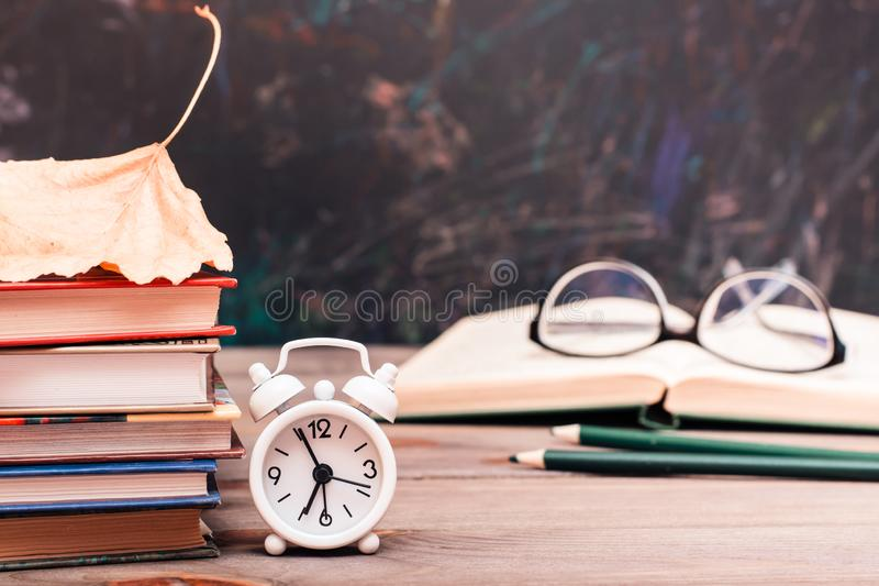 Back to school background with books, clock, fallen leaf, open book and glasses on a wooden table royalty free stock images