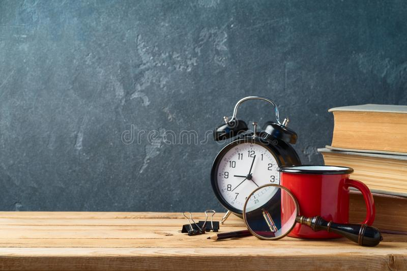 Back to school background with coffee cup, alarm clock and old books on wooden table royalty free stock image