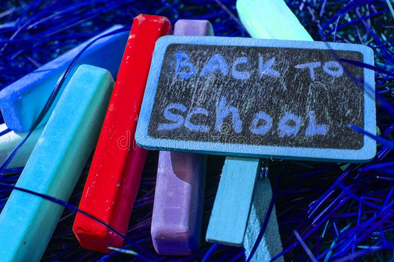 Back to school background with colorful neon colored crayons, on purple glowing background. Flat position, top view, copy space. royalty free stock images
