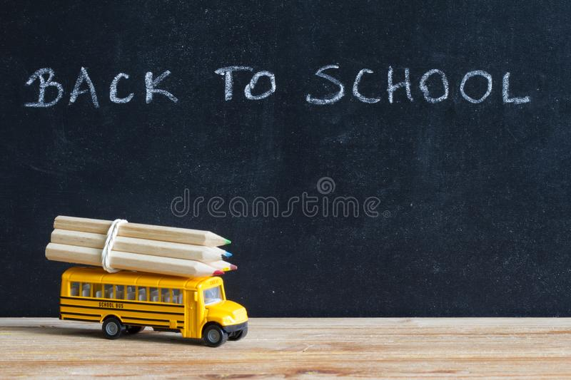 Back to school background concept with bus and accessories on blackboard royalty free stock photography