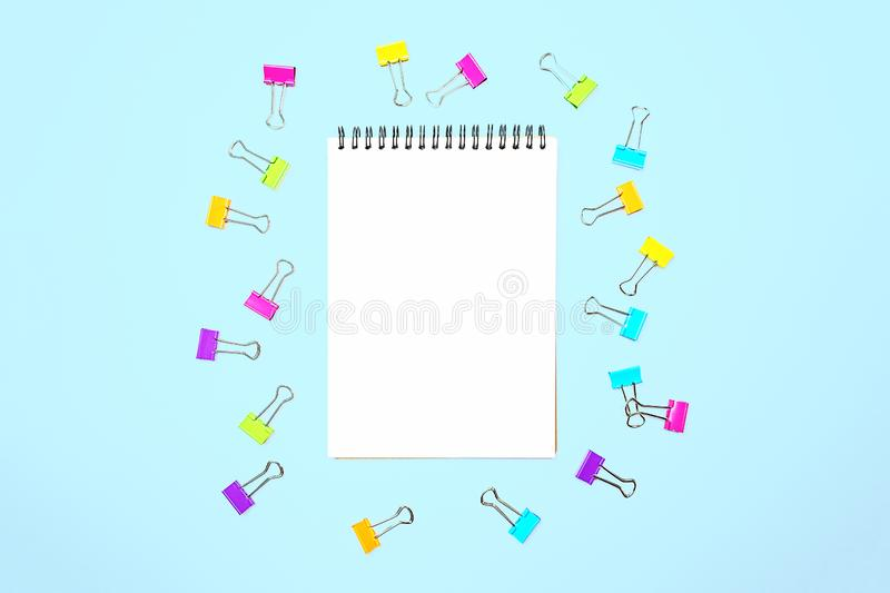 Back to school background with notepad, colorful paper clips on pastel blue backdrop. Flat lay, top view, copy space royalty free stock image