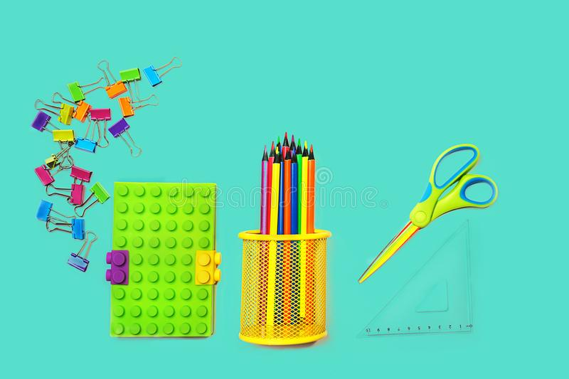 Back to school background with notepad, colorful paper clips, pencils, square ruler, scissors on pastel blue green backdrop. Flat lay, top view, copy space royalty free stock image