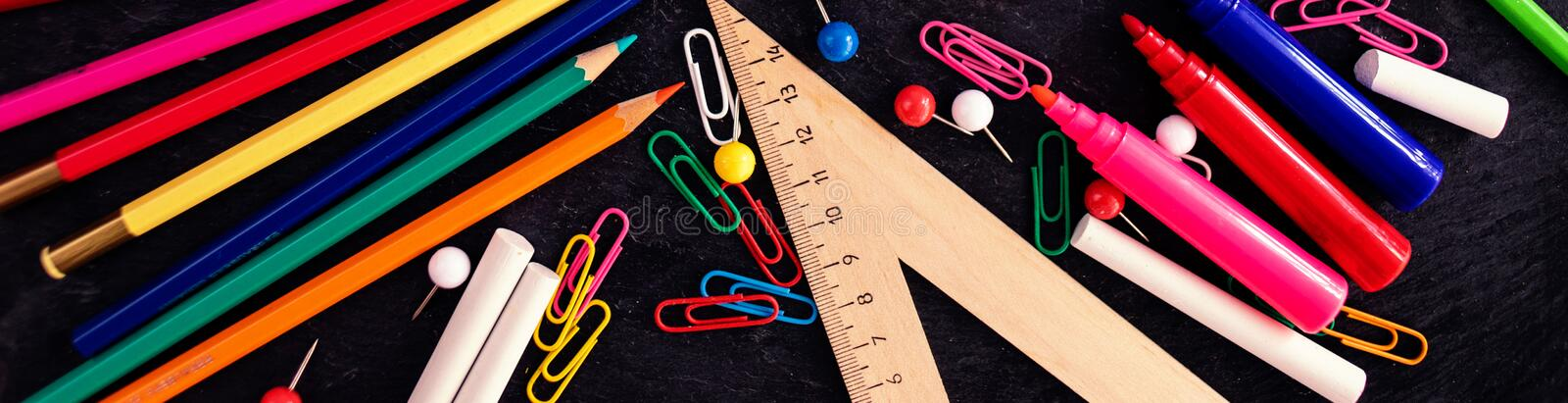 Back to School Background with school and office  supplies on black chalk board. Top view. Flat lay stock photography