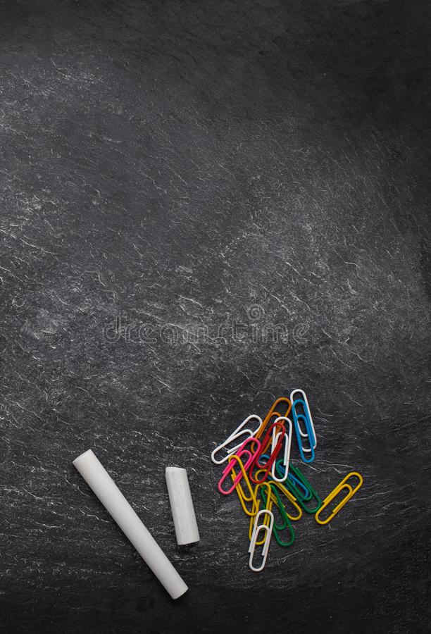 Back to school Background with paper clips and white chalk sticks on black board. School supplies for classes and lessons.  Copy royalty free stock images