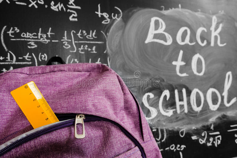 Back to school background with purple school bag with yellow ruler and the title `Back to school` and math formulas. Written by white chalk on the black school stock photos