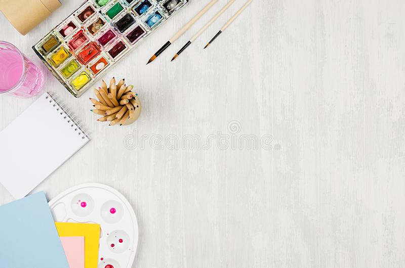 Back to school background - stationery for creativity - watercolor paints, palette, brushes, colored pencils on white wood table, stock photo
