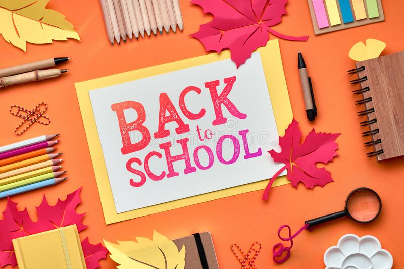 Back to school background with supplies and paper leaves, text \'Back to school. Back to school, flat lay on dark texture background with stationary and stock photo