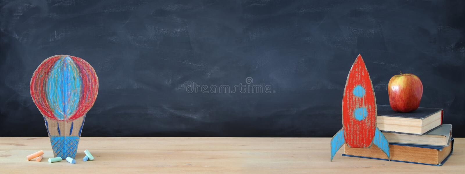 Back to school banner. Painted cardboard rocket and Hot air balloon next to books in front of classroom blackboard. stock images