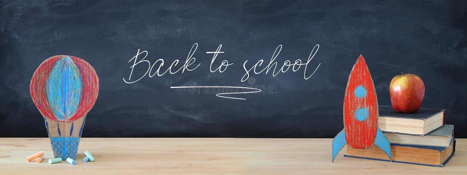 Back to school banner. Painted cardboard rocket and Hot air balloon next to books in front of classroom blackboard. stock image