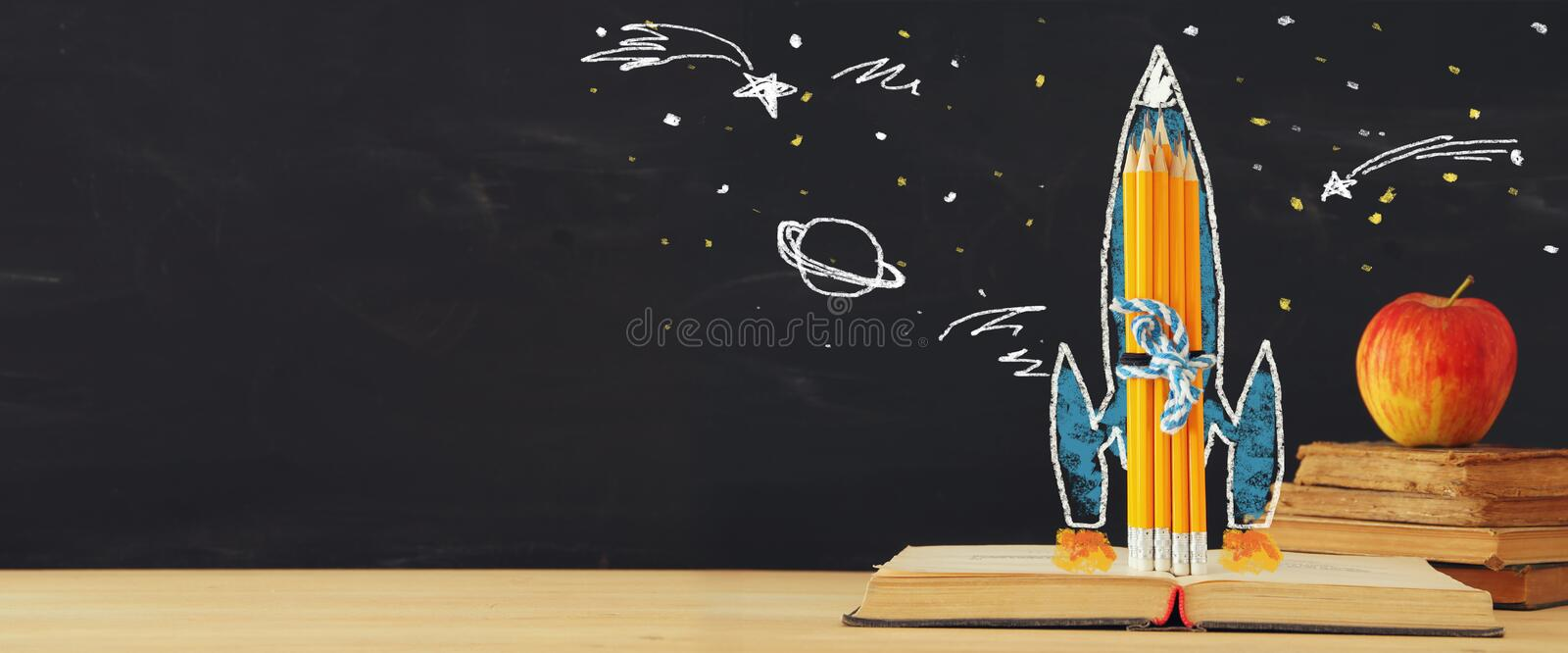 Back to school banner. rocket sketch and pencils over open book in front of classroom blackboard. royalty free stock photography