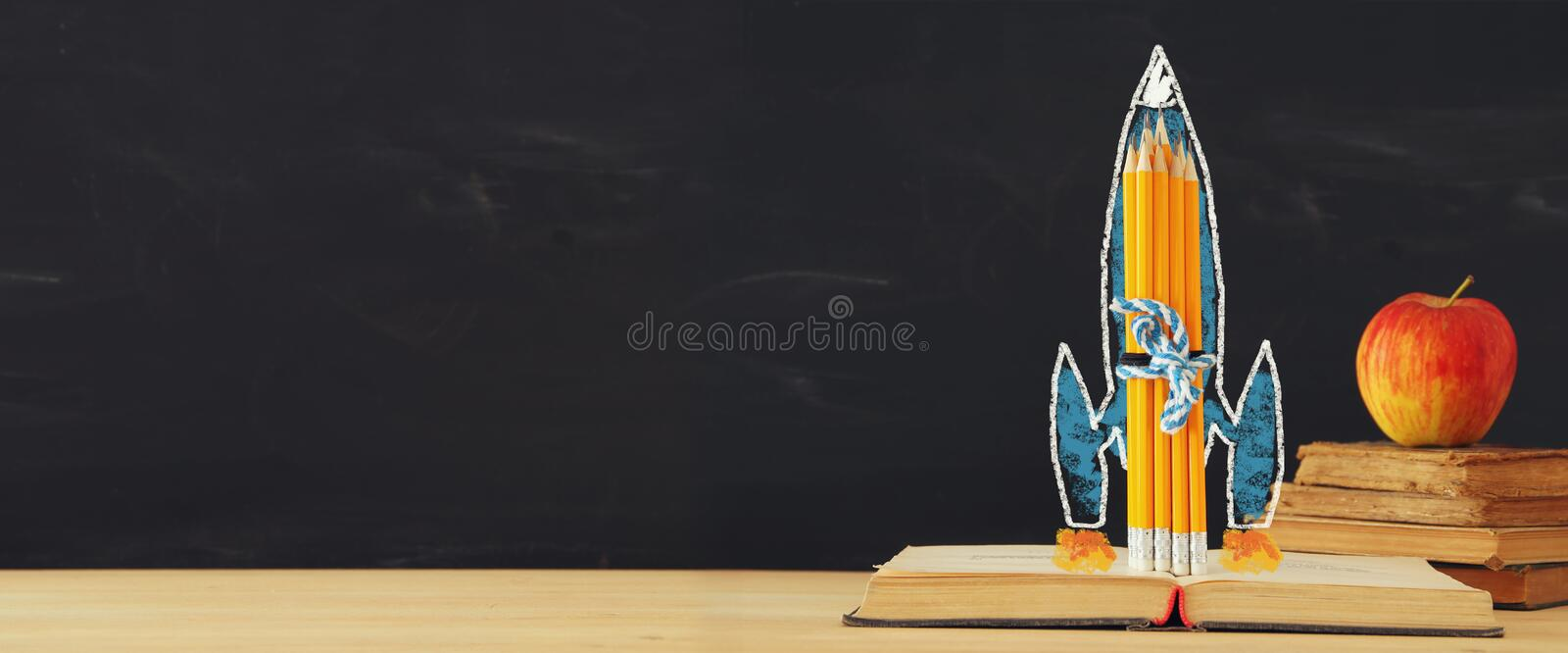 Back to school banner. rocket sketch and pencils over open book in front of classroom blackboard. royalty free stock images
