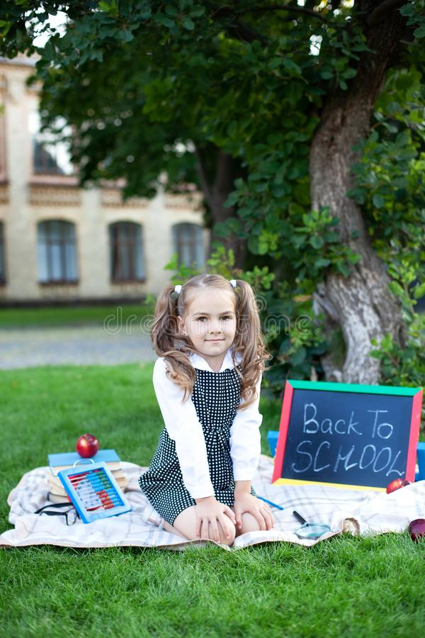 Back to school. A beautiful little schoolgirl is sitting in the grass near a school with a school office. Education concept. Presc royalty free stock photo
