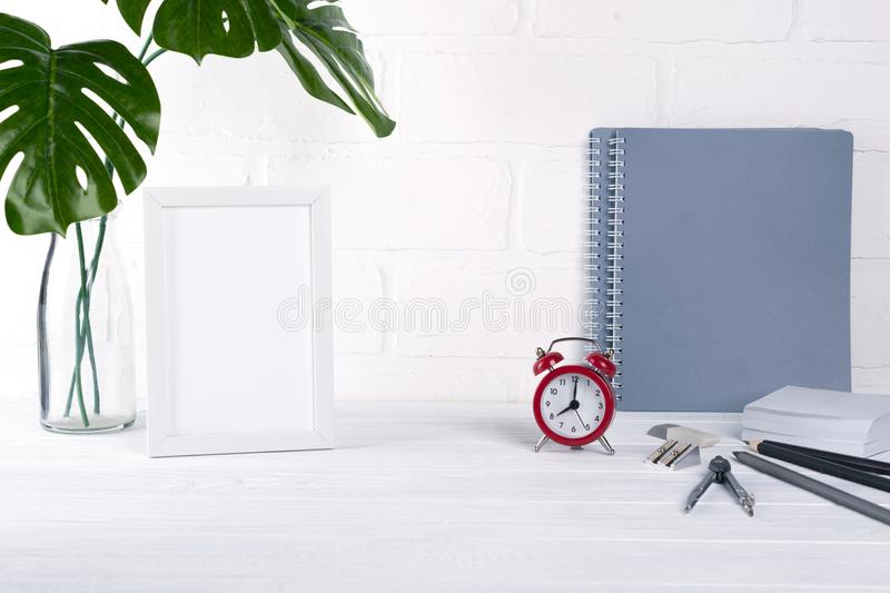 Back to school, business office education concept. Assortment of supplies, crayons, pens, notebook, alarm clock on a table. stock images