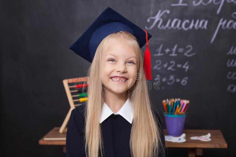 Back to school! Cheerful little girl at school on a black background. Looking into the camera. School concept. Schoolgirl in the c stock photo