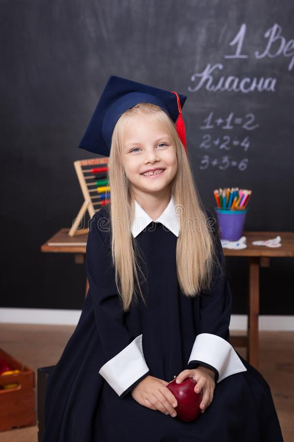 Back to school! Cheerful little girl at school on a black background. Looking into the camera. School concept. Schoolgirl in class stock photography