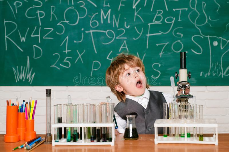 Back to school. Child in the class room with blackboard on background. Back to school and happy time. Happy smiling. Pupil drawing at the desk. First school day stock photos