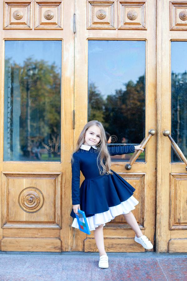 Back to school. Child education and school concept. The concept of a break. Cute little schoolgirl in a dress opens the school doo royalty free stock photo