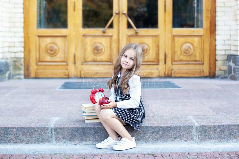Back to school. Child little girl student sits on the steps near the school and holds an apple in her hands. Schoolgirl is having. Lunch on the street royalty free stock photos