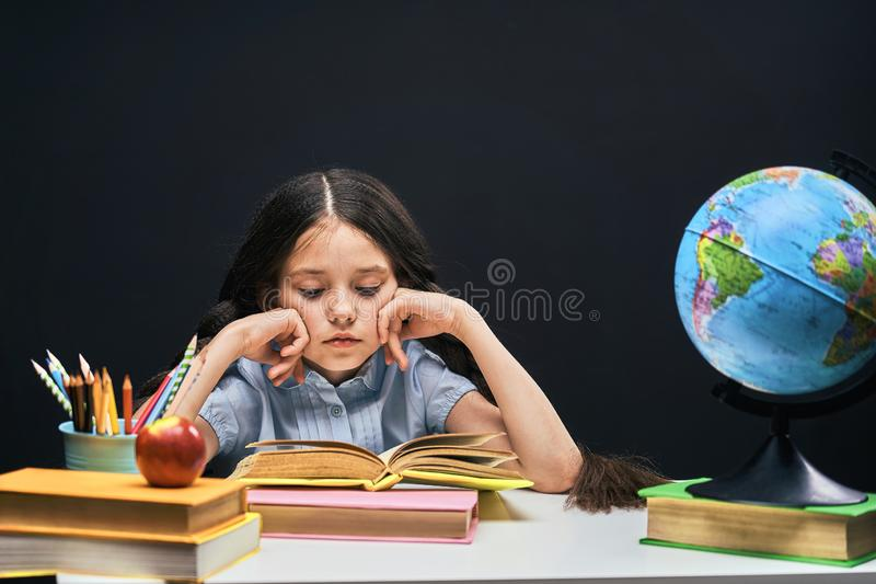 Back to school. concentrated handsome student reading a book sitting at the table. A child in the classroom with a Board in the stock photos