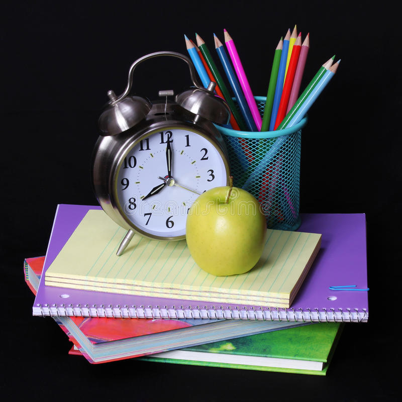 Back to school concept. An apple, colored pencils and alarm clock on pile of books over black royalty free stock photography