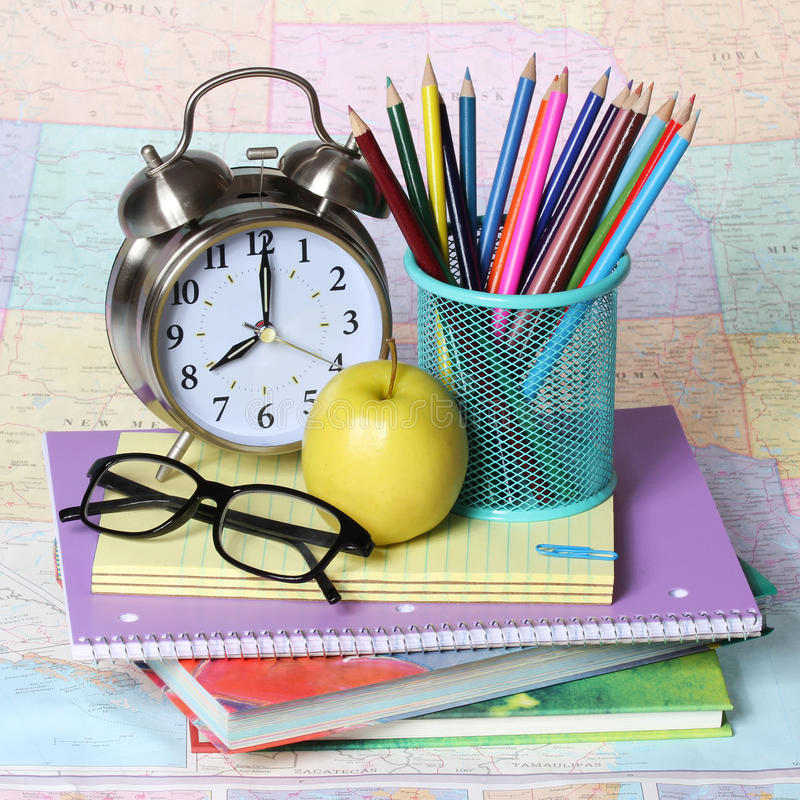 Back to school concept. apple, colored pencils, glasses and alarm clock on pile of books over the map stock photos