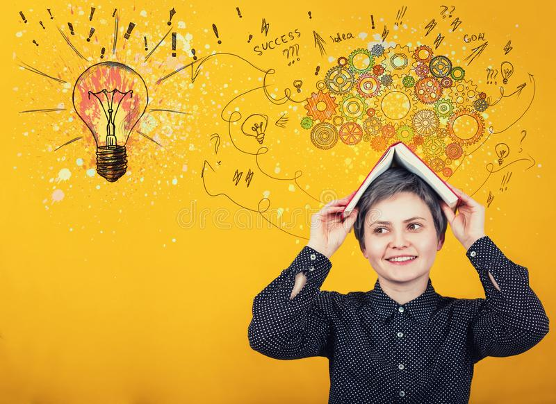 Back to school concept as happy student girl looks aside positive expression, keeps open book over head. Idea thinking as colorful. Gear brain and bulb create a stock image