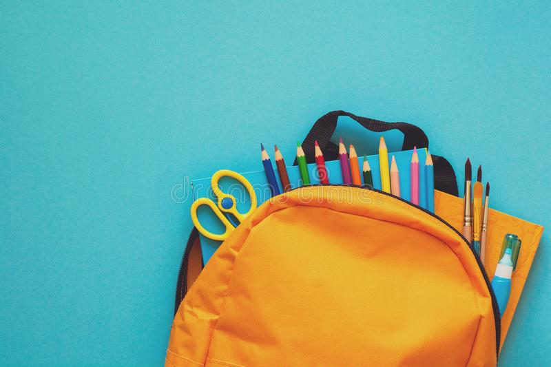 Back to school concept. Backpack with school supplies. Top view. Copy space. Toned royalty free stock images
