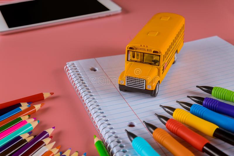 Back to school concept, school bus on notebook and pencils stock images
