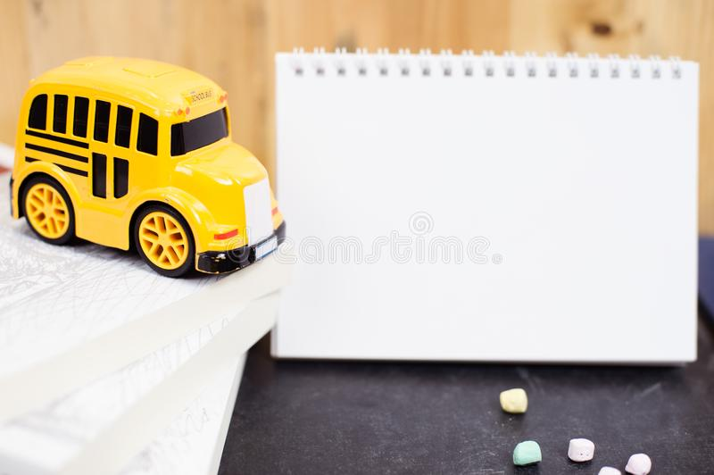 Back to school concept with school bus toy, books and blank note book. royalty free stock images