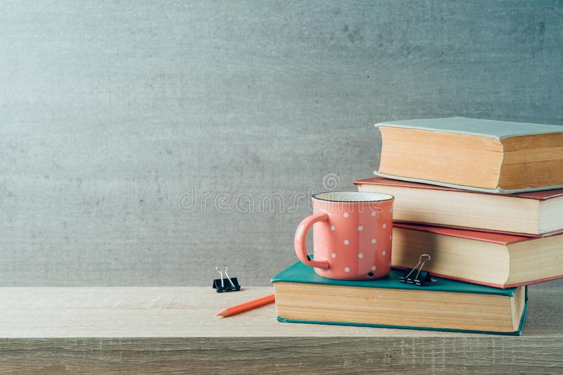 Back to school concept with coffee cup and books on wooden shelf background stock photos