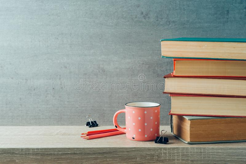 Back to school concept with coffee cup and books on wooden shelf background royalty free stock image