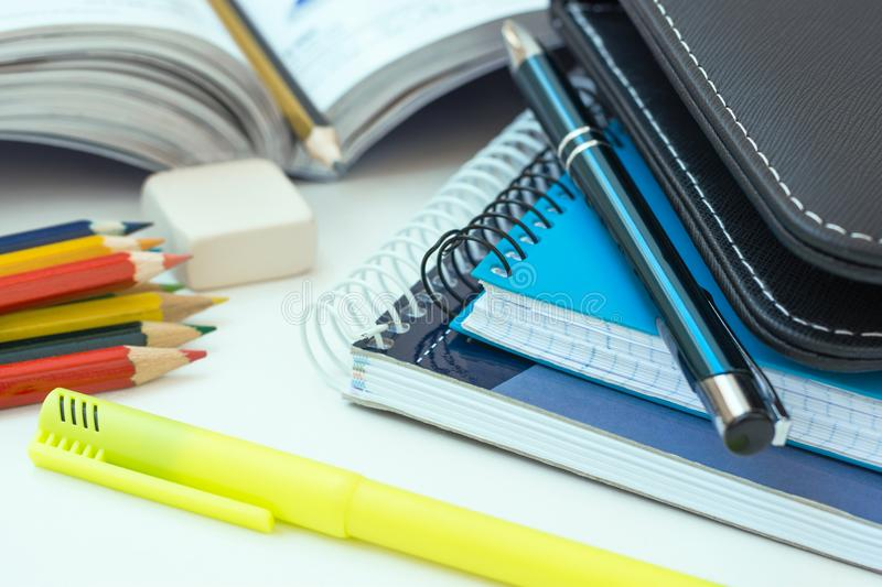 Back to School Concept. Composition from Supplies Laptop Tablet Keyboard Multicolored Pencils Highlighter Rubber Pen. Opened Workbook on White Desktop. Learning stock image