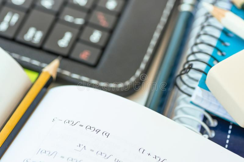 Back to School Concept. Composition from Supplies Laptop Tablet Keyboard Rubber Pen Opened Workbook with Mathematics Formula. Marked with Pencil on White stock images