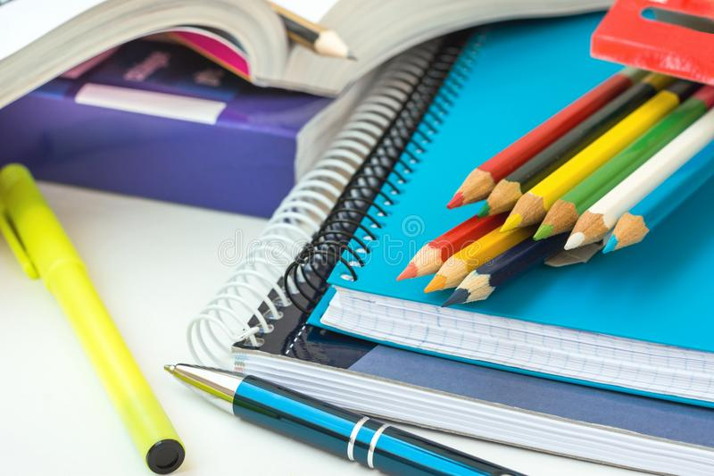 Back to School Concept. Composition from Supplies Stack of Copybooks Multicolored Pencils Highlighter Rubber Pen Opened Workbook. On White Desktop. Learning stock photos