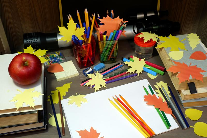 Back to school concept with empty sketchbook, colored pencils, stationary supplies and schoolbooks on brown wooden table with stock images