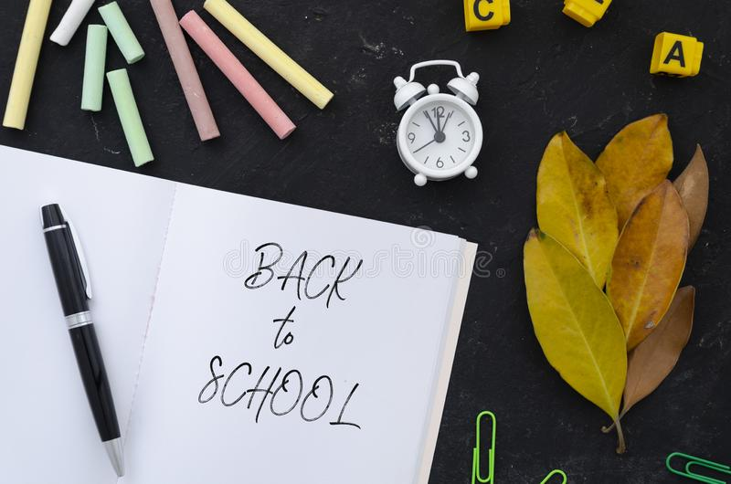 Back to school concept. Flat lay notepad with sign, chalks and autumn leaves over classroom blackboard.  stock photography