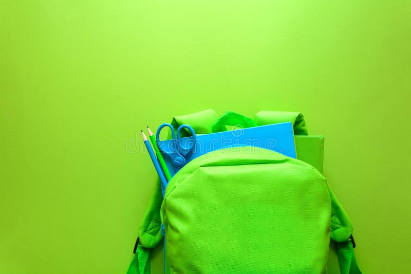Back to school concept. Green backpack with school supplies on green background. Top view. Copy space stock image