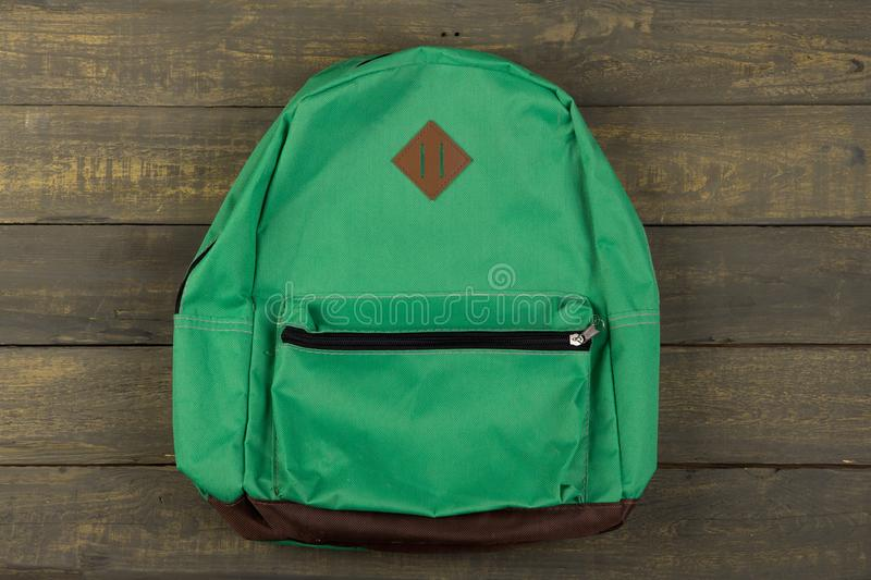 Back to school concept - green backpack on wooden backgroung royalty free stock images