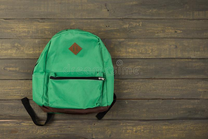 Back to school concept - green backpack on wooden backgroung royalty free stock photos