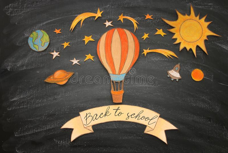 Back to school concept. Hot air balloon, space elements shapes cut from paper and painted over classroom blackboard background. Back to school concept. Hot air stock photos