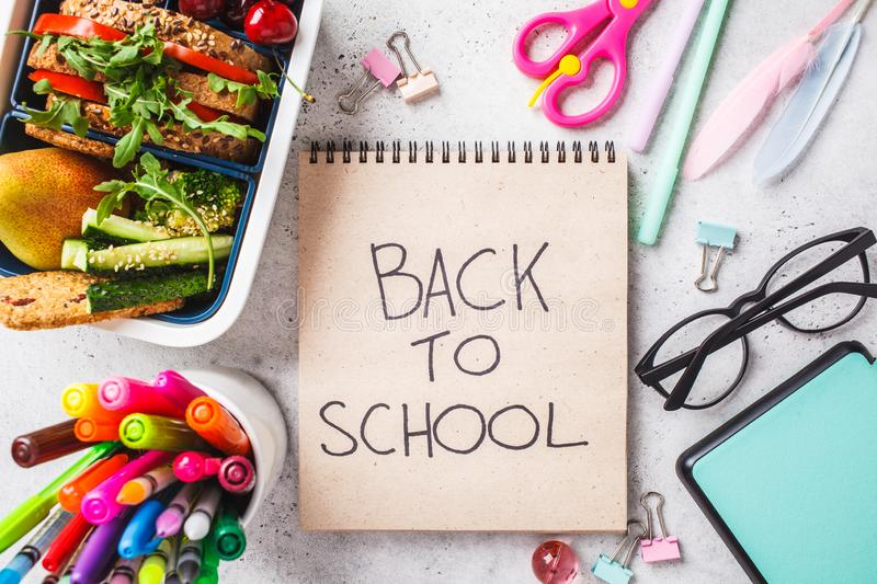 Back to school concept.  Lunch box with sandwich, fruit, snacks, notebook, pencils and school items, top view stock photos